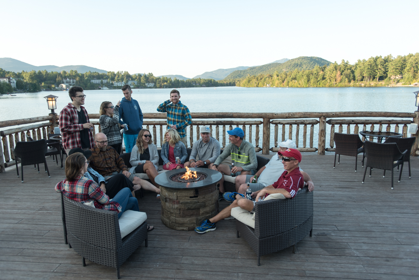 friends hanging out by firepit on boathouse