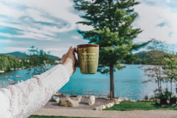 girl holding Golden Arrow mug with views of Mirror Lake