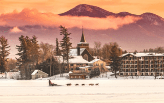 Dogs pulling a sled across Mirror Lake during sunrise